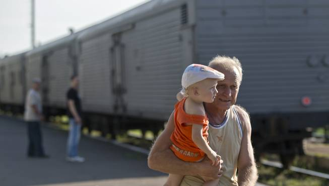 A man holds a baby as he walks next to a refrigerated train loaded with the bodies of victims, in Torez, eastern Ukraine, 15 kilometers (9 miles) from the crash site of Malaysia Airlines Flight 17, Sunday, July 20, 2014. Armed rebels forced emergency workers to hand over all 196 bodies recovered from the Malaysia Airlines crash site and had them loaded Sunday onto refrigerated train cars bound for a rebel-held city, Ukrainian officials and monitors said.