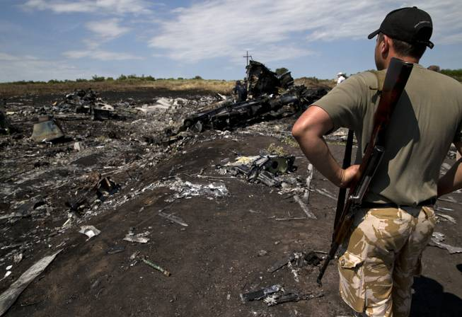 An armed man looks at charred debris at the crash site of Malaysia Airlines Flight 17 near the village of Hrabove, eastern Ukraine, Sunday, July 20, 2014. Armed rebels forced emergency workers to hand over all 196 bodies recovered from the Malaysia Airlines crash site and had them loaded Sunday onto refrigerated train cars bound for a rebel-held city, Ukrainian officials and monitors said.
