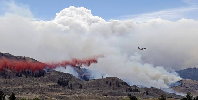 A DC-10 air tanker drops fire retardant over a wildfire as smoke rises and billows behind Saturday, July 19, 2014, near Carlton, Wash. A wind-driven, lightning-caused wildfire racing through rural north-central Washington destroyed about 100 homes Thursday and Friday, leaving behind solitary brick chimneys and burned-out automobiles as it blackened hundreds of square miles in the scenic Methow Valley northeast of Seattle.