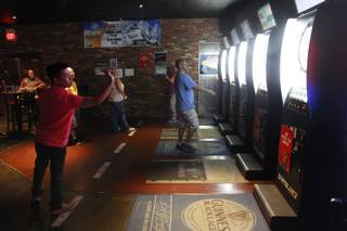 Members warm up during a meeting of the Las Vegas Darts league Wednesday, July 2, 2014 at the Crowbar.