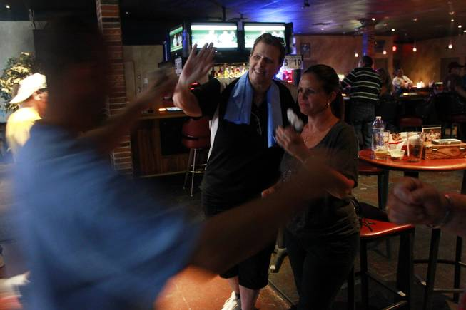 Stacy Bromberg and Lisa Boshart give Mike Brooks a high five during a meeting of the Las Vegas Darts league Wednesday, July 2, 2014 at the Crowbar.