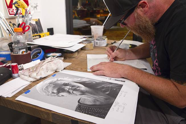 Artist JW Caldwell works on artwork based on a composite portrait in the P3 Studio in the Cosmopolitan Monday, July 21, 2014. For their project, photographer Todd Duane Miller combines portraits of people and Caldwell creates artwork from the composite photos.
