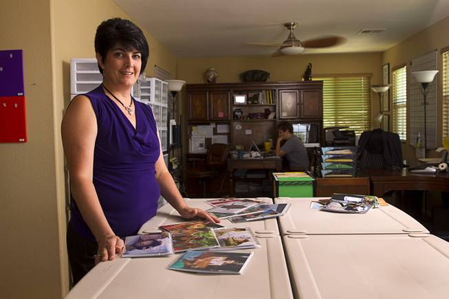"Teazled CEO Dina Proto poses with greeting cards at her office Monday, July 21, 2014. Her wife ""Dom"" Poist-Proto is at right. Teazled is a company that makes ""traditional greeting cards for nontraditional familes."""