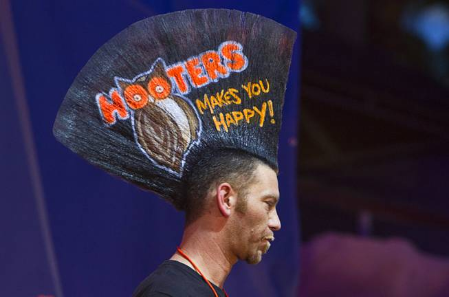 """Mohawk Man"" Chris Wallingford displays a Hooters ad on his hair during the 2014 Hooters ""World-Wide Wing Eating Championship"" at the Hard Rock pool Tuesday, July 22, 2014."