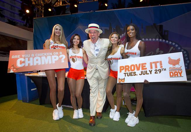 "Emcee George Shea poses with Hooters Girls during the 2014 Hooters ""World-Wide Wing Eating Championship"" at the Hard Rock pool Tuesday, July 22, 2014."