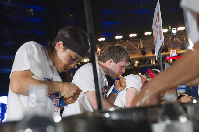 "Adrian ""The Rabbit"" Morgan, center, competes in the 2014 Hooters ""World-Wide Wing Eating Championship"" at the Hard Rock pool Tuesday, July 22, 2014."