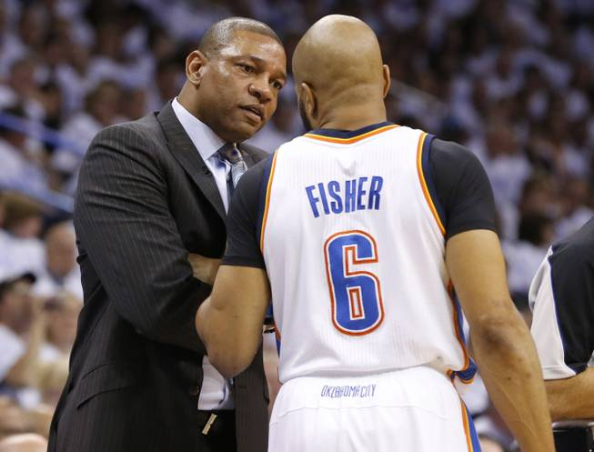 Los Angeles Clippers head coach Doc Rivers talks with Oklahoma City Thunder guard Derek Fisher (6) in the second quarter of Game 5 of the Western Conference semifinal NBA basketball playoff series in Oklahoma City, Tuesday, May 13, 2014.