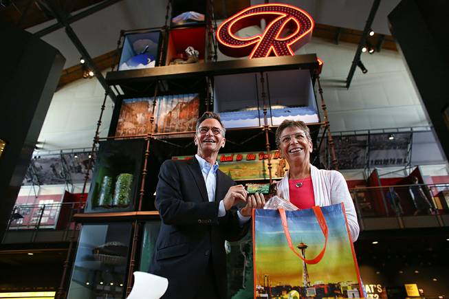 Museum of History and Industry Executive Director Leonard Garfield accepts a donation Tuesday, July 22, 2014, in Seattle of the first legal recreational marijuana purchase in Seattle from Deb Green, right, who made the purchase at Cannabis City on July 8.