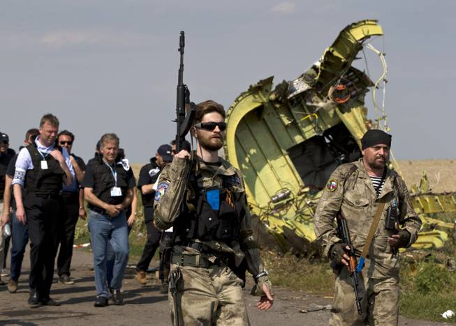 Pro-Russian rebels, right, followed by members of the OSCE mission, walk by plane wreckage as they arrive for a media briefing at the crash site of Malaysia Airlines Flight 17, near the village of Hrabove, eastern Ukraine, Tuesday, July 22, 2014. A team of Malaysian investigators visited the site along with members of the OSCE mission for the first time since last week's crash.