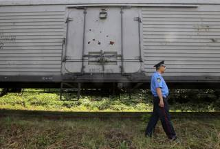 A police officer walks past a refrigerated train loaded with bodies of the passengers of Malaysian Airlines flight MH17 at Kharkiv railway station, Ukraine, Tuesday, July 22, 2014. The train carrying the remains of people killed in the Malaysia Airlines crash arrived in the eastern Ukrainian city of Kharkiv on Tuesday on their way to the Netherlands, a journey which has been agonizingly slow for relatives of the victims.