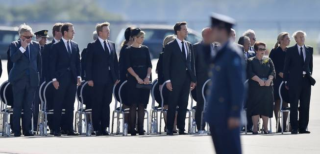 King Willem Alexander, 3rd from left, his wife Maxima and prime minister Mark Rutte, stand during a ceremony to mark the return of the first bodies, of passengers and crew killed in the downing of Malaysia Airlines Flight 17, from Ukraine at Eindhoven military air base, Netherlands, Wednesday, July 23, 2014. After being removed from the planes, the bodies are to be taken in a convoy of hearses to a military barracks in the central city of Hilversum, where forensic experts will begin the painstaking task of identifying the bodies and returning them to their loved ones.