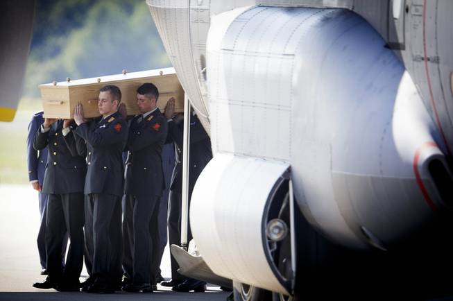 Pallbearers carry a coffin out of a military transport plane during a ceremony to mark the return of the first bodies, of passengers and crew killed in the downing of Malaysia Airlines Flight 17, from Ukraine at Eindhoven military air base, Eindhoven, Netherlands, Wednesday, July 23, 2014. After being removed from the planes, the bodies are to be taken in a convoy of hearses to a military barracks in the central city of Hilversum, where forensic experts will begin the painstaking task of identifying the bodies and returning them to their loved ones.