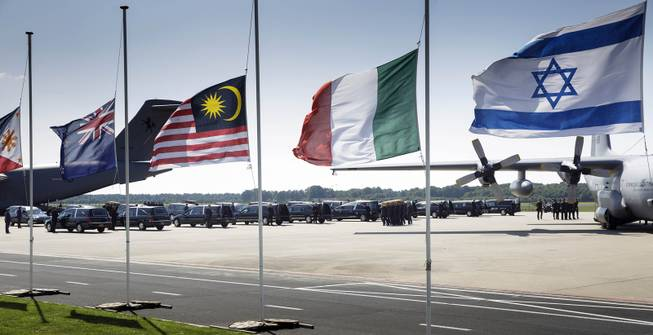 Flags fly half-staff as pallbearers carry a coffin out of a military transport plane during a ceremony to mark the return of the first bodies, of passengers and crew killed in the downing of Malaysia Airlines Flight 17, from Ukraine at Eindhoven military air base, Wednesday, July 23, 2014. After being removed from the planes, the bodies are to be taken in a convoy of hearses to a military barracks in the central city of Hilversum, where forensic experts will begin the painstaking task of identifying the bodies and returning them to their loved ones. Flags from left: Philippines, New Zealand, Malaysia, Italy and Israel.