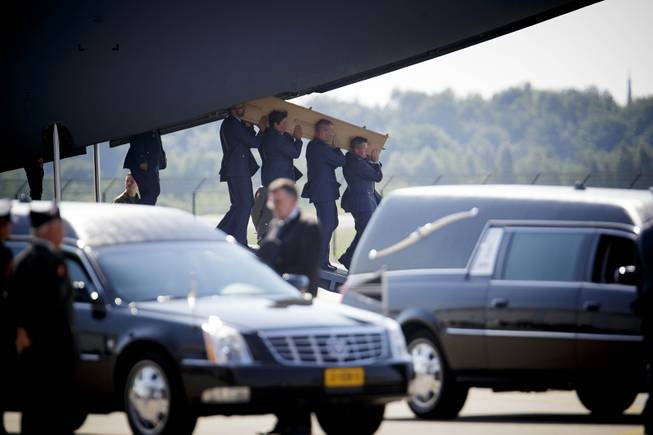 Pallbearers carry a coffin out of a military transport plane during a ceremony to mark the return of the first bodies, of passengers and crew killed in the downing of Malaysia Airlines Flight 17, from Ukraine at Eindhoven military air base, Netherlands, Wednesday, July 23, 2014. After being removed from the planes, the bodies were taken in a convoy of hearses to a military barracks in the central city of Hilversum, where forensic experts will begin the painstaking task of identifying the bodies and returning them to their loved ones.