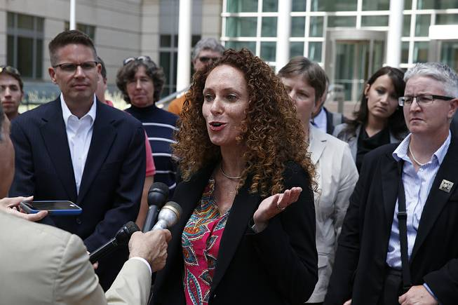 Attorney Mari Newman, center, talks with members of the media, as she stands with her plaintiffs and their supporters following a court hearing on sam sex marriage at the federal District Court, in Denver, Tuesday, July 22, 2014.