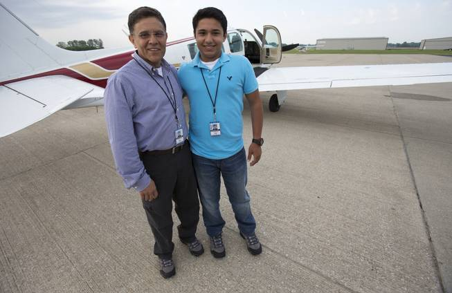 In this Thursday, June 19, 2014, photo, Babar Suleman and son Haris Suleman, 17, stand next to their plane at an airport in Greenwood, Ind., before taking off for an around-the-world flight.