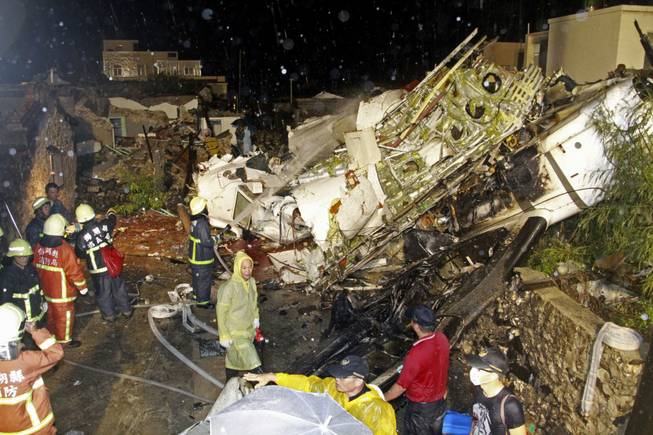 Rescue workers work next to the wreckage of TransAsia Airways flight GE222 which crashed while attempting to land in stormy weather on the Taiwanese island of Penghu, late Wednesday, July 23, 2014.