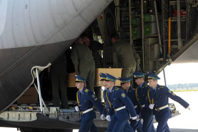 Ukrainian honor guards march away from a cargo plane, as Dutch crew members load a coffin holding the body of one of the Malaysian Airlines plane passengers in Kharkiv airport, Ukraine, Wednesday, July 23, 2014.