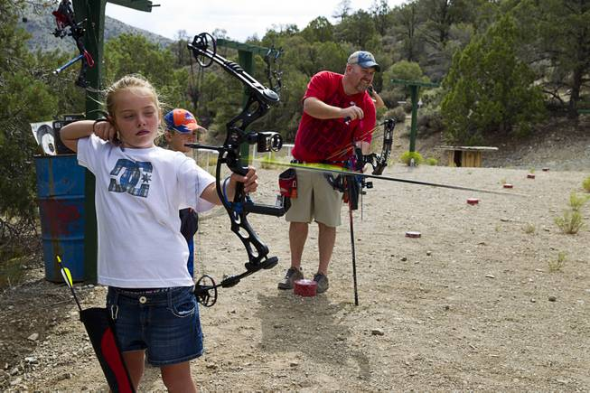 Justics Lavin, 8, lets an arrow fly at the Las Vegas Archers Spring Mountain Range near Mountain Springs Sunday, July 20, 2014. Jeremy Beard is at right.