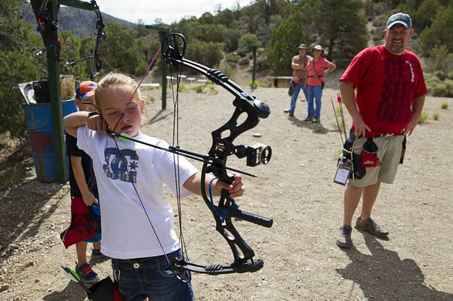 Justice Lavin, 8, takes aim at a target as Jeremy Beard looks on at the Las Vegas Archers Spring Mountain Range near Mountain Springs Sunday, July 20, 2014.