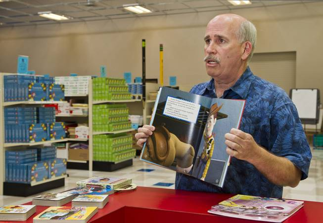 Tim McCubbin, director of the Public Education Foundation's Teacher EXCHANGE, displays one of the Spanish-language books available for teachers to purchase for cheap on Tuesday, July 22, 2014.  They are very popular items and thousands have been purchased for first and second language students.