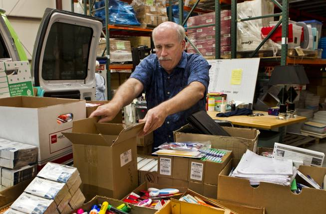 Tim McCubbin, director of the Public Education Foundation's Teacher EXCHANGE, grabs a box off the Cargo Glide installed on their Teacher Exchange Express van within the warehouse on Tuesday, July 22, 2014.