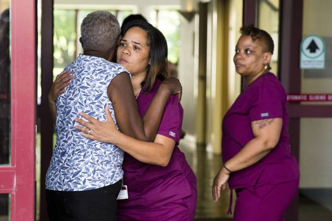 A hospital worker embraces a woman near the scene of a shooting at the Mercy Fitzgerald Hospital in Darby, Pa. on Thursday, July 24, 2014. A prosecutor said a gunman opened fire inside the psychiatric unit leaving one hospital employee dead and a second injured before being critically wounded himself.