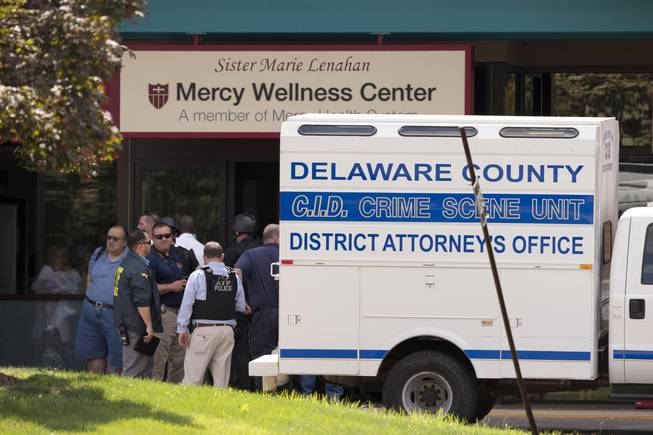 Investigators work the scene of a shooting Thursday, July 24, 2014, at Mercy Fitzgerald Hospital in Darby, Pa. A shooting at the suburban Philadelphia hospital campus has killed one worker and injured two other people. Prosecutor Jack Whelan says one of the injured is the gunman.