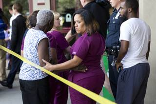A hospital worker views police activity near the scene of a shooting at a wellness center attached to Mercy Fitzgerald Hospital in Darby, Pa., on Thursday, July 24, 2014. A doctor grazed by gunfire from a patient who had entered his office in a suburban hospital's psychiatric unit stopped him by returning fire with his own gun and injuring him, authorities said.