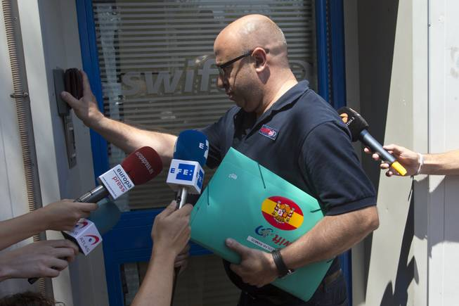 A man wearing a shirt with a Swiftair logo and carrying a Swiftair folder enters the Spanish airline's office in Madrid, Spain, Thursday, July 24, 2014. An Air Algerie flight carrying 116 people from Burkina Faso to Algeria's capital disappeared from radar early Thursday over northern Mali, officials said. The flight was being operated by Spanish airline Swiftair, the company said in a statement, and the plane belonged to Swiftair. The flight crew was Spanish.