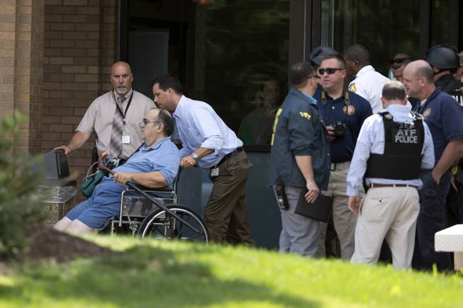 A patient is evacuated from the scene of a shooting at the Mercy Fitzgerald Hospital in Darby, Pa. on Thursday, July 24, 2014. A prosecutor said a gunman opened fire inside the psychiatric unit leaving one hospital employee dead and a second injured before being critically wounded himself.