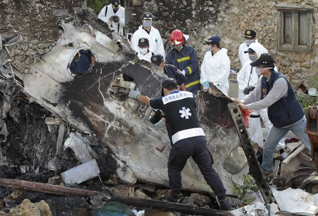 A forensic team recovers human remains among the wreckage of crashed TransAsia Airways flight GE222 on the outlying island of Penghu, Taiwan, Thursday, July 24, 2014. Stormy weather on the trailing edge of Typhoon Matmo was the likely cause of the plane crash that killed more than 40 people, the airline said Thursday.