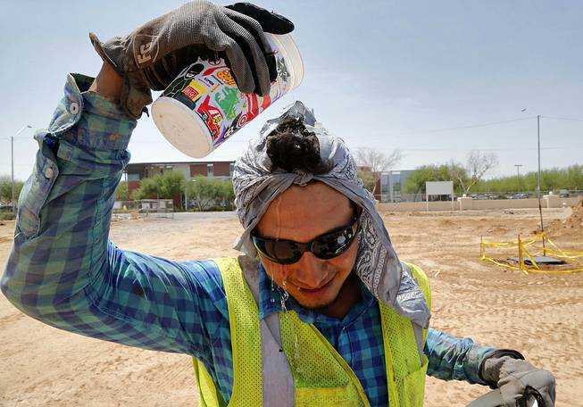 Construction worker Ruben Roman drips water on his head during his lunch break, Thursday, July 24, 2014, at at job site in Phoenix. With Phoenix-area daytime highs hovering around 110 degrees, outdoor activity is minimal throughout the valley.