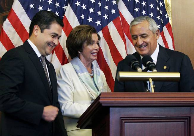 House Democratic Leader Nancy Pelosi, D-Calif., center, is seen with Guatemalan President Otto Molina, right, and Honduran President Juan Hernández on Thursday, July 24, 2014 on Capitol Hill in Washington. The Obama administration is weighing giving refugee status to young people from Honduras as part of a plan to slow the influx of unaccompanied minors arriving at the U.S.-Mexico border, White House officials said Thursday.