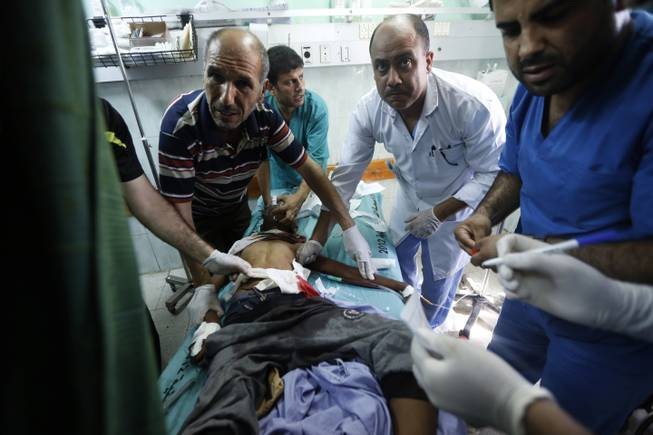 Palestinian medics treat a child wounded in an Israeli strike on a compound housing a U.N. school in Beit Hanoun, in the northern Gaza Strip, at the emergency room of the Kamal Adwan hospital in Beit Lahiya, Thursday, July 24, 2014.