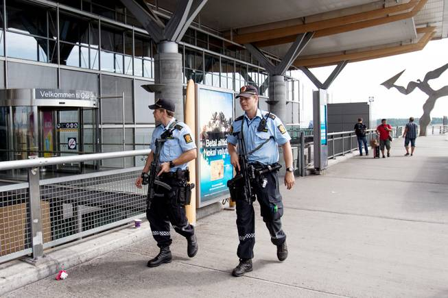 "Armed police patrol outside the terminal building at Oslo Airport, Thursday, July 24, 2014. Norway's intelligence service says it has been warned of an imminent ""concrete threat"" against the nation from people with links to Islamic fighters in Syria."