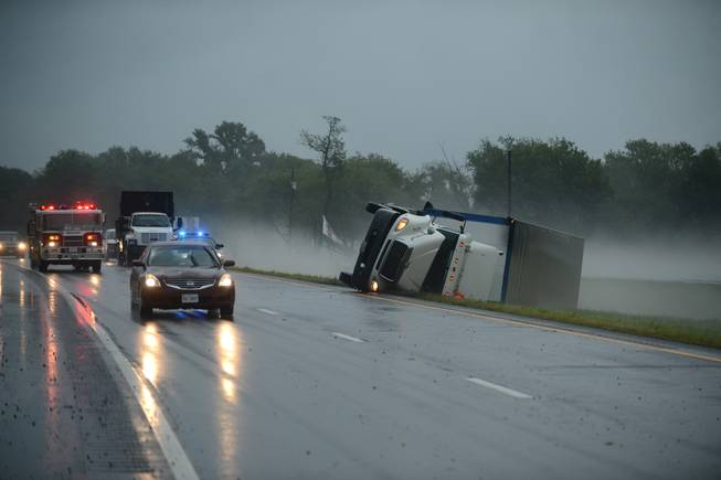 A tractor trailer truck lies on its side in the median of U.S. Route 13 in Cheriton, Va., while a fire engine responds to a nearby campground after a severe storm passed through the area, Thursday, July 24, 2014.