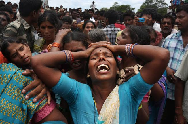 AP10ThingsToSee - A relative of a victim cries at the site of a train that crashed into a school bus in Medak district in the southern Indian state of Telengana, Thursday, July 24, 2014. Twelve children were killed in the crash at an unmanned railroad crossing in southern India, police said.