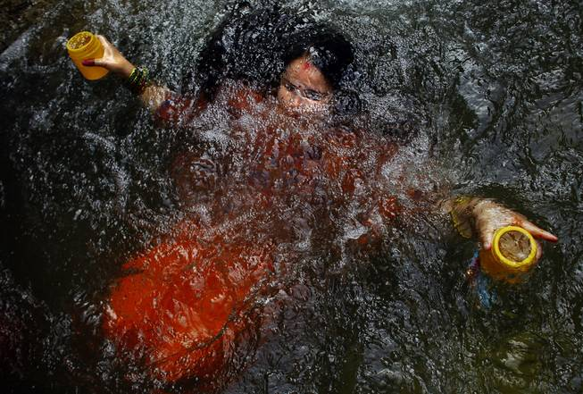 AP10ThingsToSee - A Hindu devotee takes holy dip as she collects holy water from the Bagmati river during the Bol Bom pilgrimage in Sundarijaal on the outskirts of Katmandu, Nepal, Monday, July 21, 2014. Devotees walk miles barefooted before offering the water at the Pashupatinath lord Shiva temple in Katmandu.