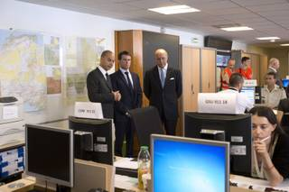 French Prime Minister Manuel Valls, center, speaks with French Foreign Affairs minister Laurent Fabius, right, and director of the French Foreign Affairs ministry's crisis center Didier Le Bret as they visit the French Foreign Affairs ministry's crisis center in Paris Friday, July 25, 2014, after a plane crashed in Mali. At least 116 people were killed in Thursday's disaster, nearly half of whom were French. One of two black boxes was recovered from the wreckage in the Gossi region of Mali near the border with Burkina Faso, and was taken to the northern city of Gao, where a French contingent is based.