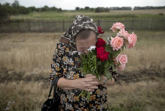 AP10ThingsToSee - A woman cries during a religious service held by villagers in memory of the victims at the crash site of Malaysia Airlines Flight 17, near the village of Hrabove, eastern Ukraine, Tuesday, July 22, 2014.