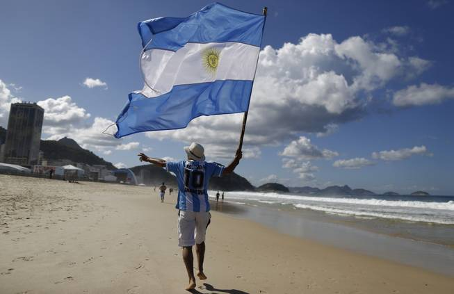 In this July 14, 2014, file photo, an Argentina soccer fan waves Argentina's national flag the morning after his team was defeated by Germany at the World Cup final, on Copacabana beach in Rio de Janeiro, Brazil. Local media reports say tens of thousands of Argentine fans have remained in the country after the tournament ended. But the prospect of a large number of foreigners selling handicrafts, juggling at intersections for handouts or relying on government social services for poor Brazilians has officials worried.