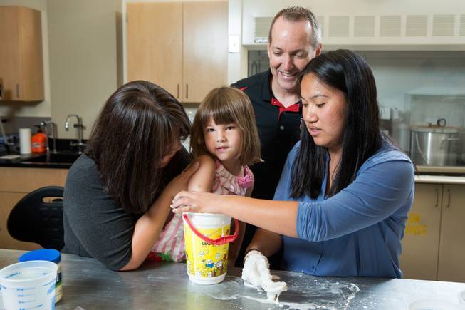 UNLV Professor Brendan O'Toole, top, and Katherine Lau, an undergraduate intern from Rutgers University, right, join Yong Dawson in helping to take measurements from Dawson's 4-year-old daughter Hailey Dawson in O'Toole's lab June 19, 2014 at the University of Nevada, Las Vegas.