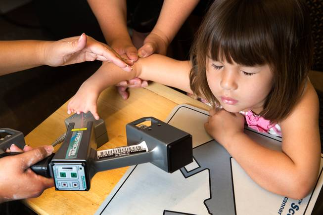 Hailey Dawson closes her eyes as a laser scanner is used to make a 3D model of her deformed hand June 19, 2014 at the University of Nevada, Las Vegas.