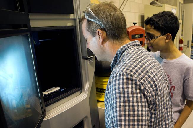 UNLV Professor Brendan O'Toole, left, and Kahrem Trabia, a high school senior at A-Tech and summer program participant, check the progress made on parts of the prototype Robohand being printed on a 3D printer June 19, 2014 at the University of Nevada, Las Vegas.