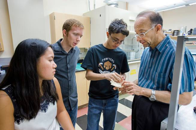 From left, Katherine Lau, a visiting undergraduate student researcher from Rutgers University and a graduate of Palo Verde High School, Zack Cook, an undergraduate Mechanical Engineering student at UNLV, Kahrem Trabia, a high school senior at A-Tech, and Dr. Mohammed Trabia, associate dean for engineering research, discuss the prototype Robohand July 23, 2014 at the University of Nevada, Las Vegas.