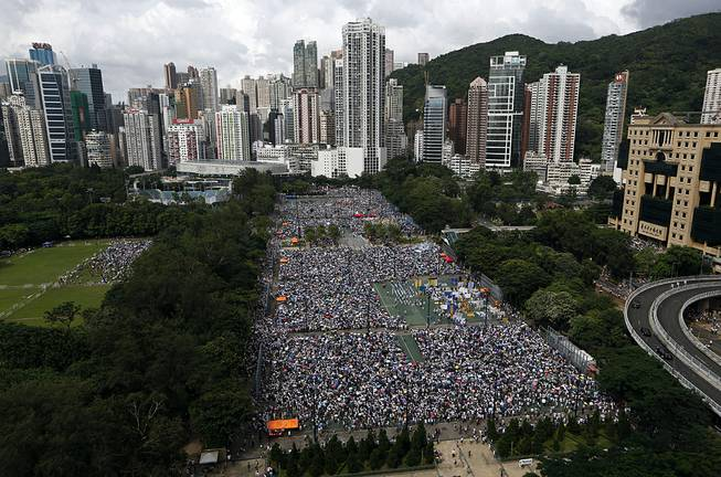 In this July 1, 2014 photo, tens of thousands of residents gather to march in downtown streets during an annual pro-democracy protest in Hong Kong to push for greater democracy. Many in this prosperous city had already feared that Hong Kong's future as an open society as well as a semiautonomous part of China was in jeopardy in the face of perceived growing intervention from Beijing.