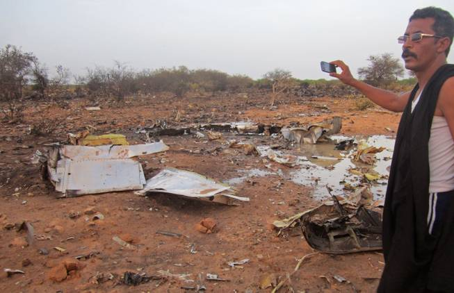 This photo provided on Friday, July 25, 2014, by the Burkina Faso Military shows a man at the site of the plane crash in Mali. French soldiers secured a black box from the Air Algerie wreckage site in a desolate region of restive northern Mali on Friday, the French president said.