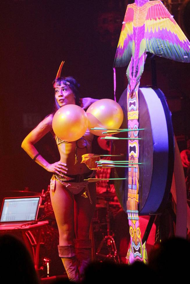 "Naomi Gesmundo of the crossbow artist duo of Mr. and Mrs. G stand with a couple of targets for her husband, Ottavio, in Melody Sweets' video-release party for the music video ""Shoot 'em Up"" at the ""Absinthe"" tent at Caesars Palace on Tuesday, July 22, 2014."