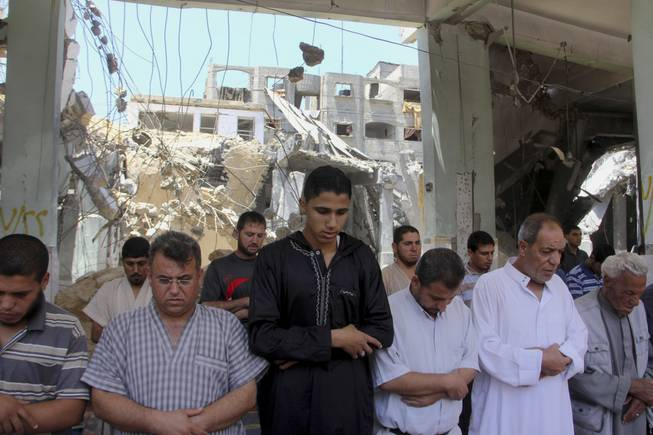 Palestinians pray Friday, July 25, 2014, inside an Al Farouk mosque destroyed by an overnight Israeli strike on Tuesday, July, 22, 2014, in Rafah in the southern Gaza Strip.